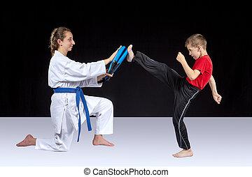 Small athlete trains a kick on the simulator