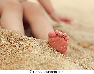 Small baby feet on the sand background