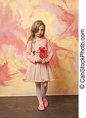 small baby girl holding valentines day decorative red hearts