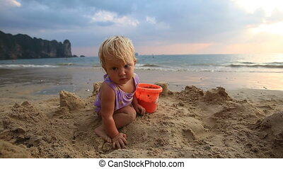 girl in purple swimsuit play in the sand