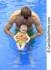 Small baby girl is swimming in the pool with daddy for the first time. Three months old baby.