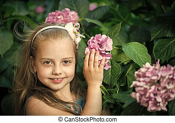small baby girl with smiling face among pink hydrangea blossom