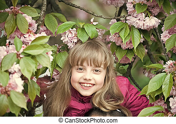 small baby girl with smiling face among pink sakura blossom