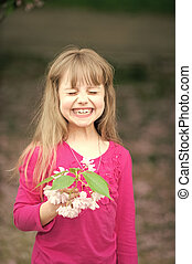 small baby girl with smiling face holding pink sakura blossom