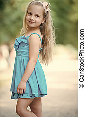 small baby girl with smiling face in blue dress outdoor
