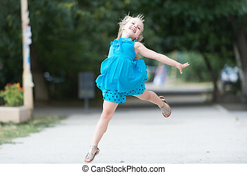 small baby girl with smiling face jumping in blue dress