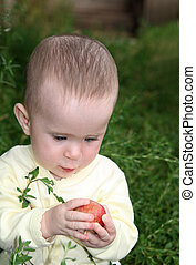 small baby holding apple