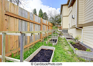 Small backyard garden bed wih wooden trellis and grid