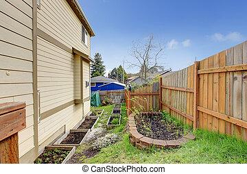 Small backyard garden bed wih wooden trellis. View of flower bed