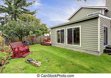 Small backyard with red wooden bench
