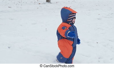 Small beautiful baby falls into the snow. Mom helps son to rise. Boy warmly dressed in overalls, he was about a year. Concept winter Activity