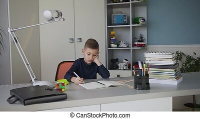 Small beautiful boy studying or doing homework, schoolboy studying with notebook and books on table. Cute beautiful pupil learning his lessons at home