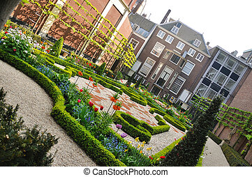 Small beautiful garden with bushes and flowers in Amsterdam, Holland (Netherlands)