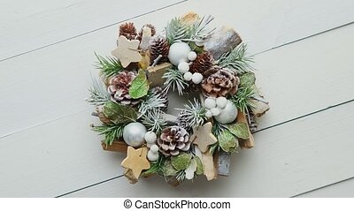 Small beautiful wreath placed on white wooden table. Christmas concept. Top view. Flat lay