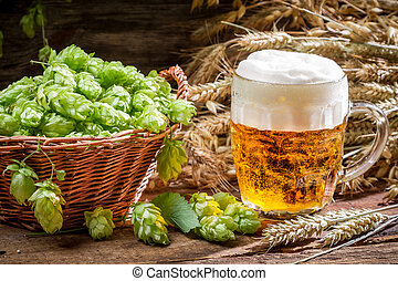 Small beer with a large foam surrounded by hops