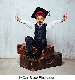 small black boy in  graduation hat sits on the old suitcases and swing hands