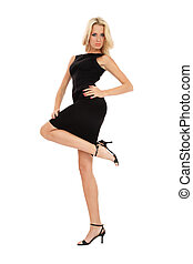 Beautiful slim blonde girl in black cocktail dress standing on white background