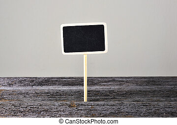 Small blackboard on the rusty wooden table