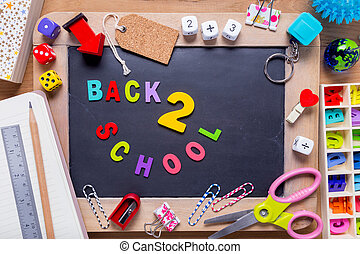 Small blackboard surrounded with various stationary with Back 2 School words in the middle