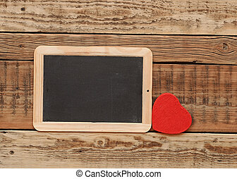 small blackboard  with a red heart on wooden wall