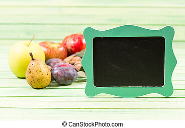 Small blackboard with frame and autumn fruits