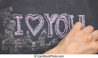 Small blackboard with the text i love you written on it in chalk. Stroke along the contour with chalk.