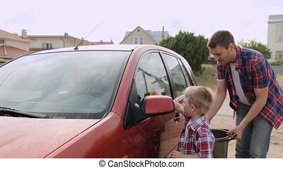 Small blond kid l washes the car's headlight under the...
