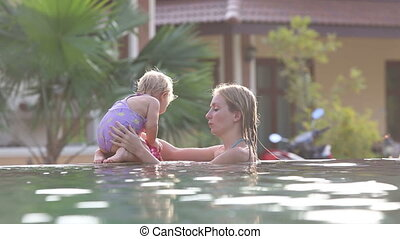 small blonde child play with mother