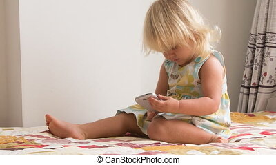 small blonde girl plays with smartphone
