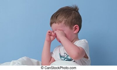 Small blonde upset boy is crying and wiping tears from his eyes with his hands while sitting in bed in morning. Child had terrible dream and he is crying. Boy is tear because he doesn't want to sleep.