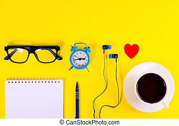 Small blue alarm clock, red paper heart, blue earphones, blue Eyeglasses and note book with blue pen, lies on bright yellow background. Coffee cup. Remote work.
