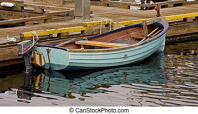 Small Blue Boat at a Pier - A small blue fishing boat tied ...