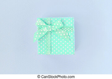 Small blue gift box with ribbon lies on a violet background