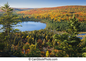 Small blue lake amid hills in autumn color