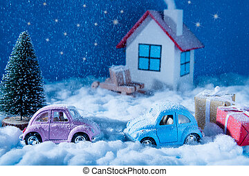 Small blue pink toy cars stand outdoors on snowy weather with red yellow giftboxes green pine tree white joyful family celebrate christmas eve in white comfort house over blue sky background
