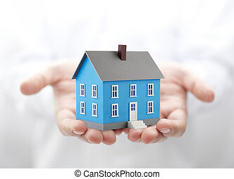 Small blue toy house in hands