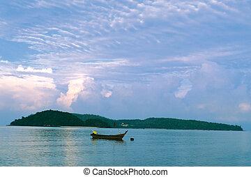 small boat in the sea at sunrise