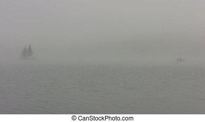 small boat on foggy lake