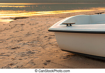 small boat on the beach with the sea at sunset