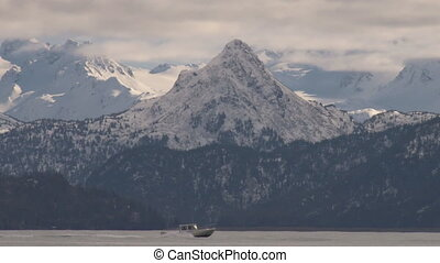 A diminuitive fishing boat zooms across the waters of Kachemak Bay with the Kenai Mountains in fine form beyond.