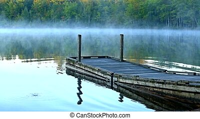 Video of a small boat ramp dock at Toddy Pond, Maine rocking and sending out gentle waves with a small bubble burst in the foreground.