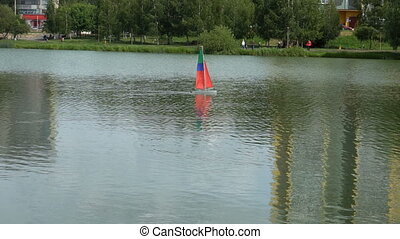 small boat-sailboat on the radio swims in the lake