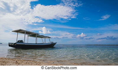 small boat with a roof standing next to a sandy beach in the open ocean, where there are small waves