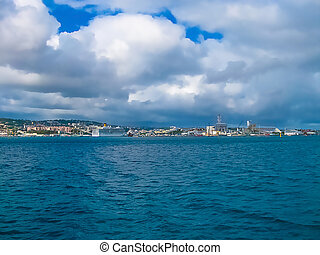 Small boats and many colorful buildings on the coast of ...