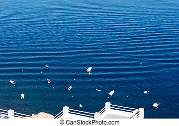 Small boats in the Mediterranean Sea off the island of Santorini