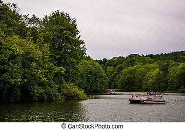Small boats near the shore of a cove on Lake Marburg, in Codorus State Park, Pennsylvania.