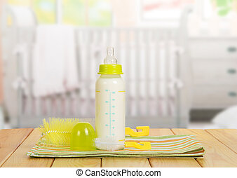 Small bottle with  nipple and milk, brush for washing dishes in the background
