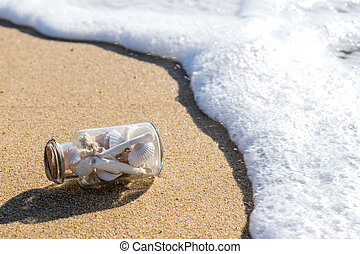 Small bottle with shells on the beach in the waves.