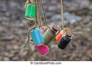 small bottles with colored sand hang on string