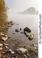 small boulders on foggy shore in autumn
